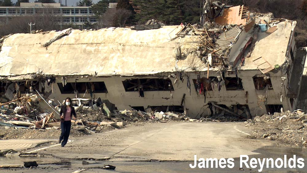 Woman runs from destroyed building in Onagawa city