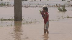 Young girl stands in flood waters in Tuguegarao in aftermath of typhoon Megi