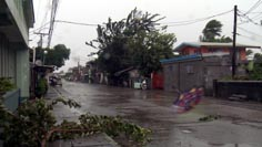 Umbrella flies down a street in Aparri, Philippines as typhoon Megi nears