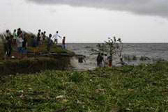Residents retrieve housing materials from storm surge in Laguna de Bay